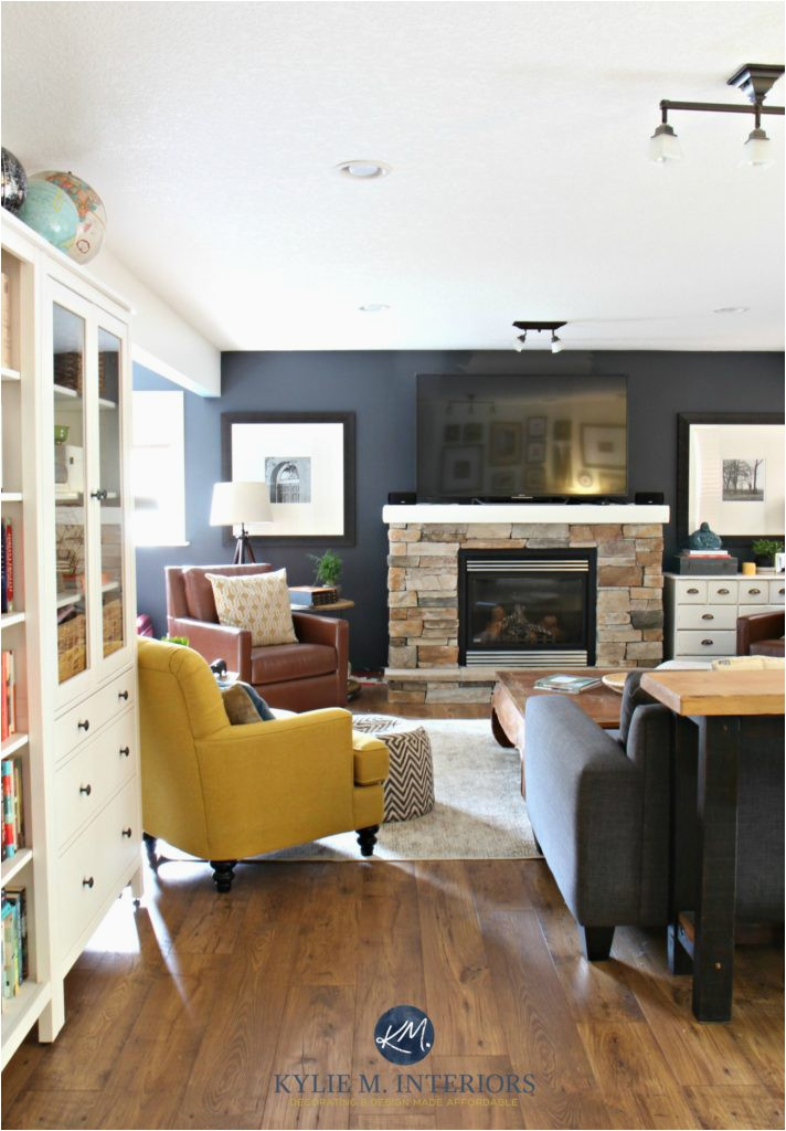 Family room with stone fireplace Sherwin Williams Cyberspace leather laminate wood flooring chartreuse chair Kylie M INteriors E design and home 1 712x1024