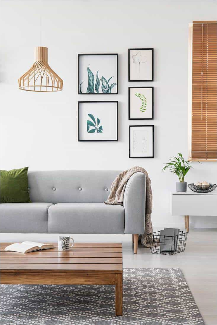 Posters on a wall in a living room interior with grey sofa and low coffee table